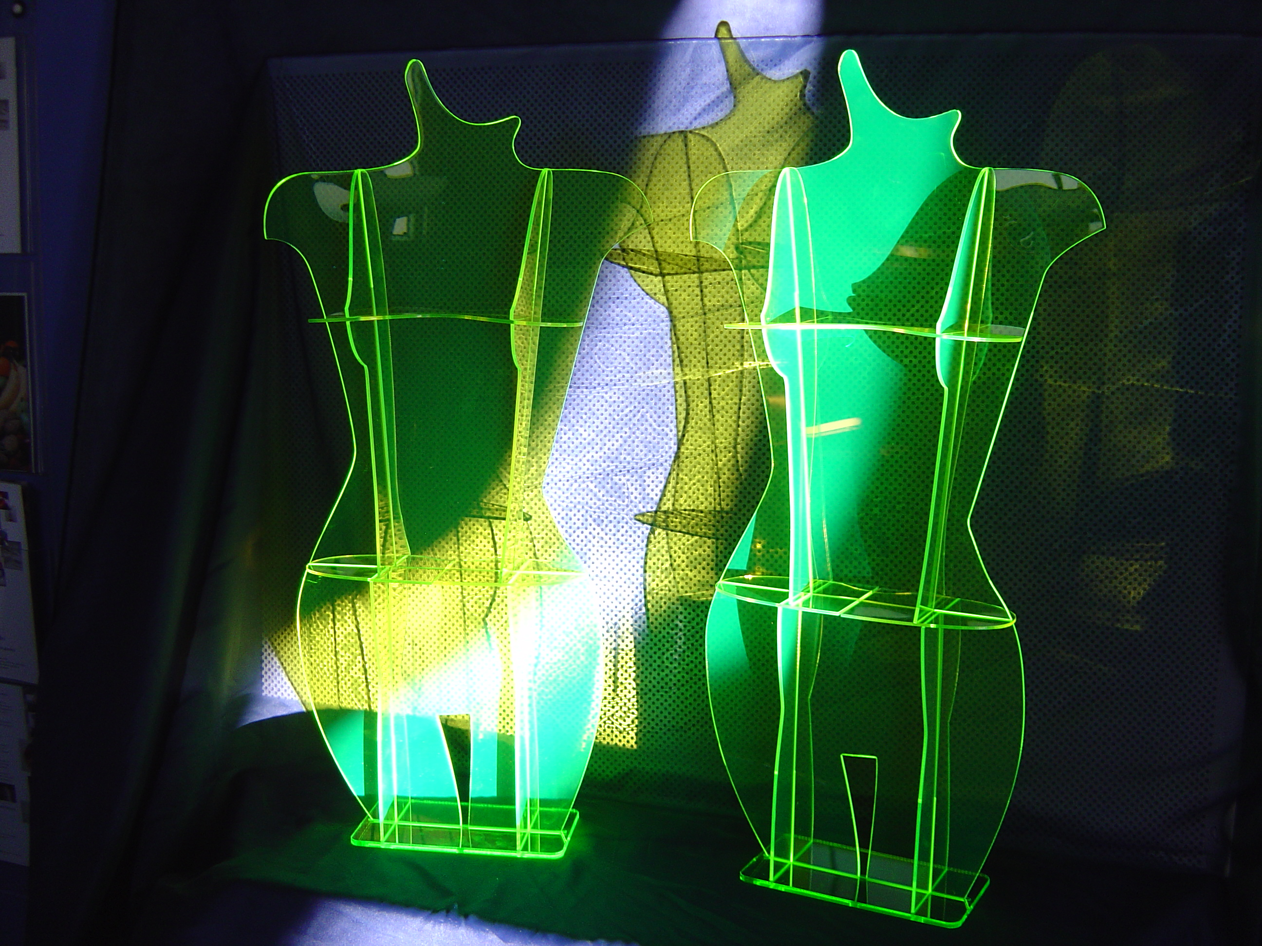 Neon green display pieces shaped like female bodies